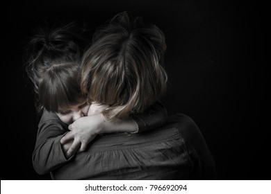 Photo shooting indoors. On a black background. Child ( girl ) hugs his mother.
