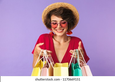 Photo of shopaholic woman 20s in straw hat holding colorful paper shopping bags with purchases isolated over violet background