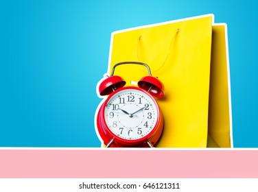 photo of shopping bag and alarm clock on the wonderful blue studio background