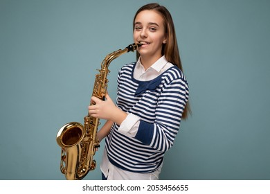 Photo shot of beautiful happy smiling brunette little girl wearing striped longsleeve standing isolated over blue background wall playing saxophone looking at camera