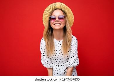 Photo shot of beautiful positive young blonde woman wearing summer casual clothes and stylish sunglasses isolated over colorful background looking at camera