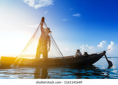 Photo shot of fisherman while throwing fishing net on the lake. Silhouette of fisherman with fishing net in morning sunshine. Stop motion water drop.