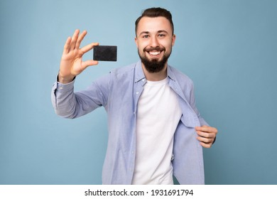 photo shot of Handsome smiling brunette bearded young man wearing stylish blue shirt and white t-shirt isolated over blue background wall holding credit card looking at camera