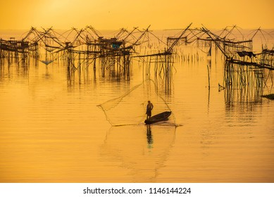 Photo shot stop motion of fisherman throwing fishing net on the lake with fish catch net as background. Silhouette of fisherman with fishing net in morning sunshine.