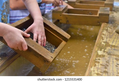 A photo showing a child's hand using a gold sifter panning for gold and gems a great educational outdoor acitivity with kids