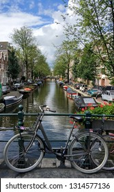 A photo showing a standing bicycle on one of the bridges in Amsterdam. In the background a canal with beautiful old wooden boats. Picture taken on a beautiful cloudy day