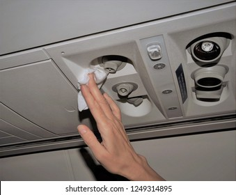 Photo showing woman's hand cleaning the air vents in an airplane with a white disinfectant wipe