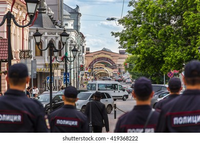 The photo shows the back of police patrolling the streets of Kazan, the building of the central market, theater, advertising signs, cars and city residents. Kazan, Bauman str., Russia, June 11, 2015