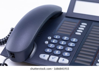 The photo shows a black telephone isolated on a white background