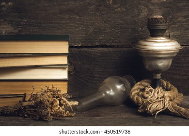The photo shows book, herbage and old lamp