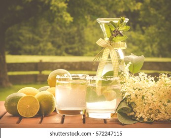 photo shows a closeup of yummy homemade elderflower refreshing drink decorated with elder blossom, lemons; garden fence and apple tree at the background