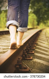 The photo shows the feet of a girl which goes on rails/ Women's feet on the rails/ Girl goes on rails