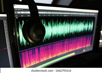 The photo shows headphones and in the back ground waveform in adobe audition.  Częstochowa / Poland - July 2019