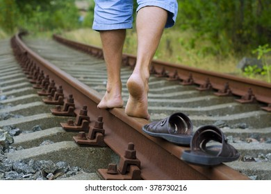 The photo shows his legs which goes on rails/ Men's feet on the rails/ The man is on rails