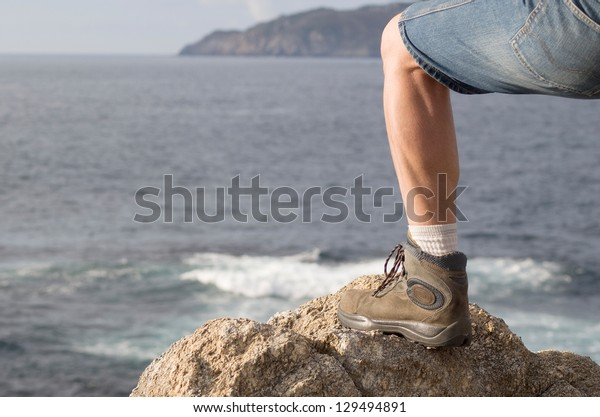 The photo shows a leg on a rock at a seascape