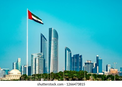 The photo shows the skyline of Abu Dhabi, taken from seaside. A AEU flag is waving in the foreground.