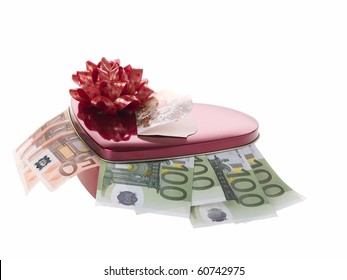 The photo shows some banknotes and a container in form of a heart over white