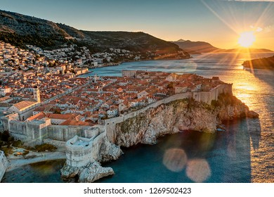 Photo shows sunrise at Croatia Dubrovnik with morning sun shinning through the old town. Photo also show the blue sea water and clear sky.