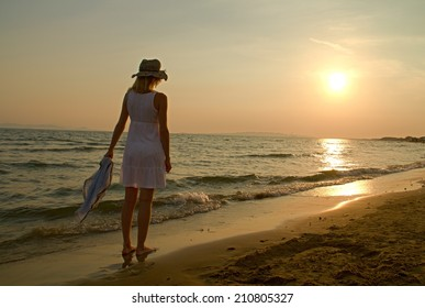 Photo shows a sunset above the beach and sea.