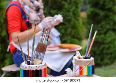 Photo shows thin and thick brush for oil and acrylic paints and pencils that stands with other artistic objects in colored jar and that lying on gray table in park in open air against girl artist