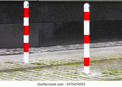 The photo shows two red and white road bollards in daylight
