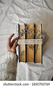 the photo shows a woman's hand. fingers gently touch the stack of books wrapped in lace ribbon. The ribbon also features dried violet flowers that accentuate the sophistication of the photograph. obje