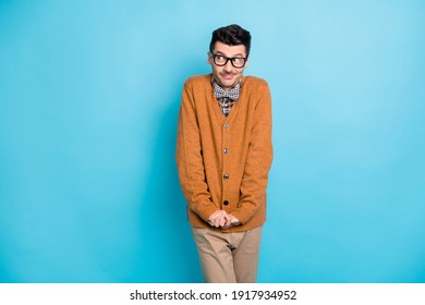 Photo of shy modest man look empty space hold hands together wear sweater pants isolated on blue color background