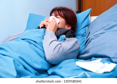 Photo of side of sick brunette girl blowing her nose in paper handkerchief lying in bed .