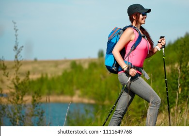 Photo of side view of young sports girl with walking sticks on background of lake and green vegetation