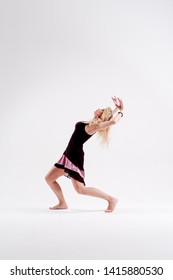 Photo from side of young dancing blonde with arms raised and looking up in studio