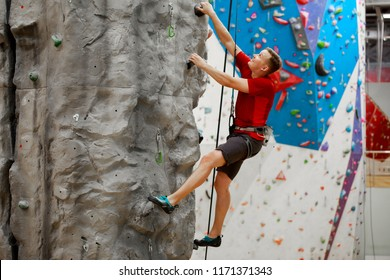 Photo from side of young sports male exercising on climbing wall
