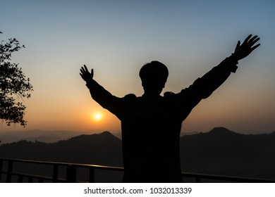Photo of silhouette adult man in profile on morning background, Silhouette of man with raised hands over sunset background.