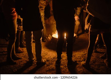 Photo of a the silhouette of a group of people standing around a bonfire
