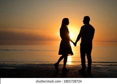 photo silhouette of a love couple. sunset, lake, romantic. portrait of a young woman and a man beach. - Shutterstock ID 1801728724