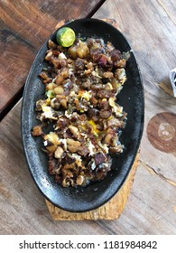 Photo of  sisig, a Filipino dish made from parts of pig head and liver, usually seasoned with calamansi and chili peppers, served on a sizzling plate on wooden table viewed from top.