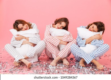 Photo of sleepy women 20s wearing leisure clothings holding pillows and taking pleasure during slumber party isolated over pink background