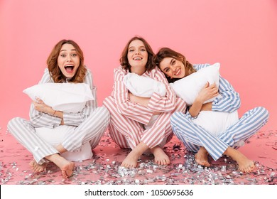 Photo of sleepy women 20s wearing leisure clothings sitting on floor with legs crossed and hugging pillows during slumber party isolated over pink background