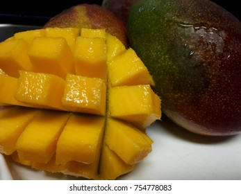photo of sliced. mango cubes with whole mangoes in the background on a white plate