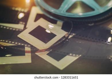 Photo slides, film negatives and 8mm or super 8 vintage film reel on a wood table with soft lights.