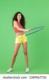 Photo of slim woman 20s wearing summer clothes doing exercises with hula hoop during gymnastics against green wall