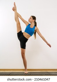 Photo of a slim woman dancer training and doing standing splits.