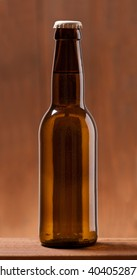 Photo of an small Bottle of beer on wooden table dark lighted up background. Studio shot indoors . No label