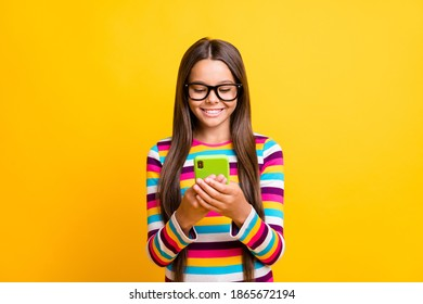 Photo of small girl hold telephone look screen white smile wear specs striped shirt isolated yellow color background