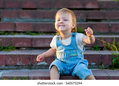 Photo of small girl sitting on stairs in the park , playing outdoors in summer time, enjoying being in nature