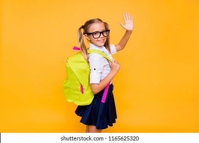 Photo of small girl turned around half a turn and waving hand look at camera isolated on bright yellow background with copy space for text