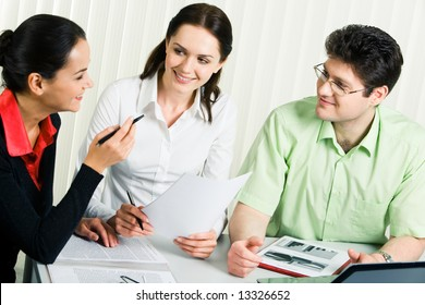 Photo of smart business team sitting around table and discussing documents in the office