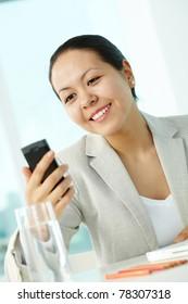Photo of smart businesswoman holding mobile phone and looking at it