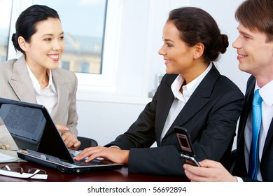 Photo of smart partners interviewing pretty Asian female in office