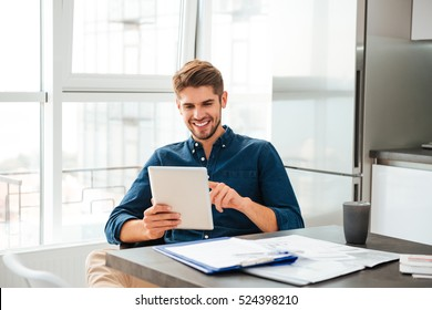 Photo of smart young man looking at tablet and sitting near table with documents.
