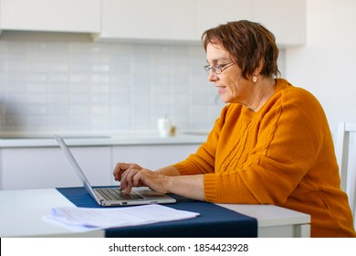 Photo of a smiley senior woman filling forms online in home interior. Online working.